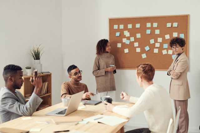 a women delegating responsibilties to other employees at a meeting