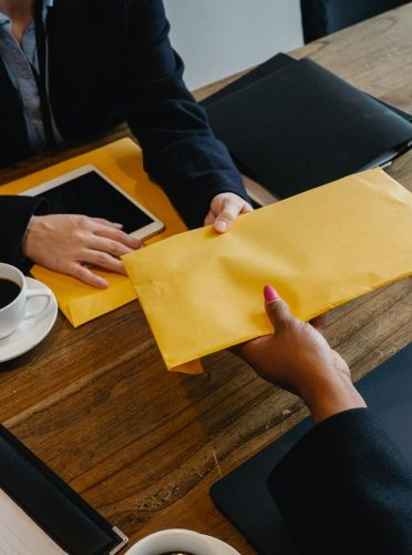 an employer handing over an monetary envelope to the employee