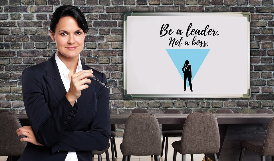 A lady standing in front of a board that states - be a leader not a boss