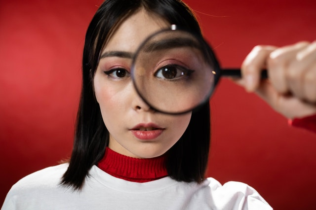 a girl looking through a magnifying glass depicting critical observation skills