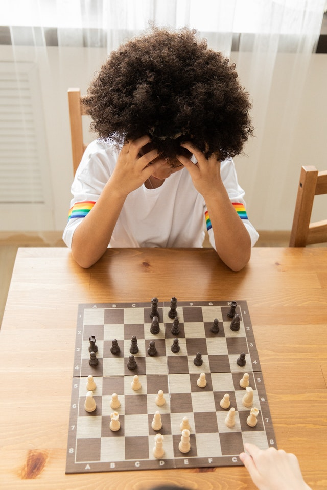 a child applying critical thinking skills while playing chess