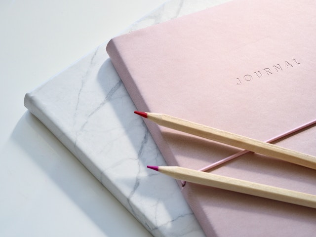 Two pencils kept on a Pink colored Journal.