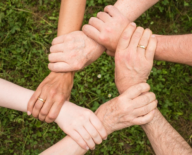 The image shows people holding hands depicting collaboration skills