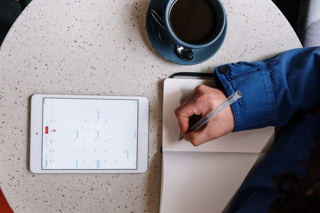 A person scheduling tasks with a Tab calendar in front of him.